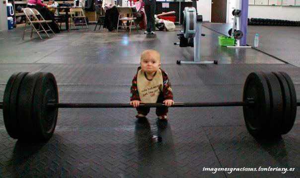 un bebe intentando levantar unas pesas de 200 kg