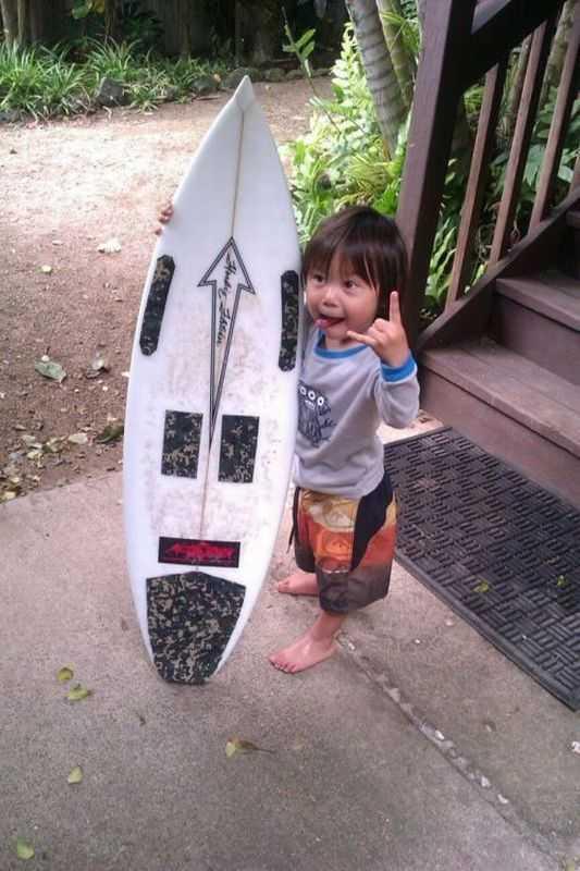 Un niño con una tabla de surf mas grande que el