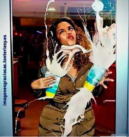 una mujer se da de morros contra una puerta de cristal