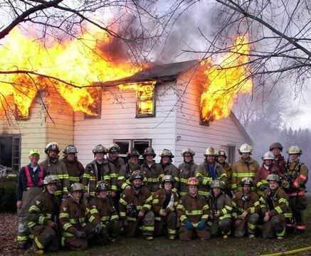 foto del cuerpo de bomberos y edificio ardiendo tras ellos