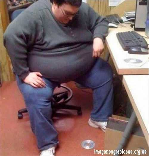 Un hombre un tanto grueso se ve mal para recoger un cd que se le ha caido