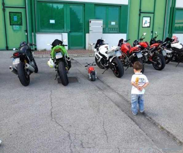 niño mirando su moto entre autenticas motos de carretera